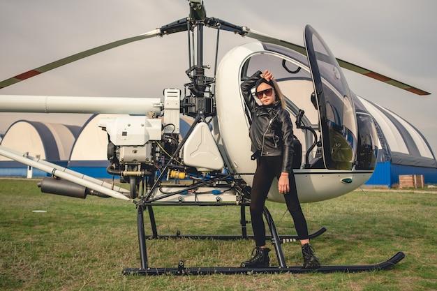 Tween dziewczyna w czarnych ubraniach stojąca w pobliżu helikoptera