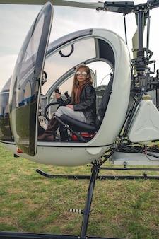 Tween dziewczyna w lustrzanych okularach siedząca na fotelu pilota w helikopterze