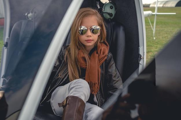 Tween dziewczyna w lustrzanych okularach siedzi w otwartym helikopterze