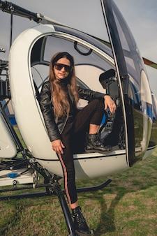 Tween dziewczyna w okularach przeciwsłonecznych siedząca w otwartym kokpicie helikoptera