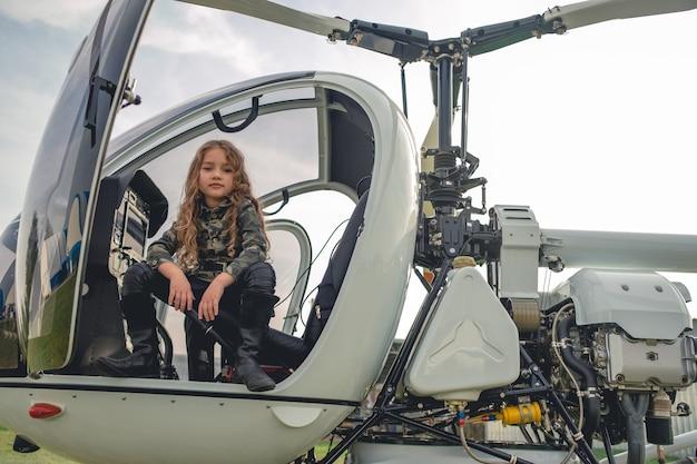 Tween dziewczyna w tunice w stylu kamuflażu siedząca w otwartym kokpicie helikoptera