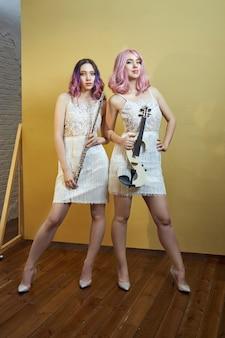Two girl muzyk ze skrzypcami i fletem w rękach jasnych strojów scenicznych. kobieta gra na współczesnych skrzypcach i flecie