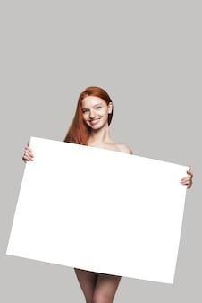 Twój tekst tutaj ładna młoda ruda kobieta trzyma pustą pustą tablicę i uśmiecha się stojąc