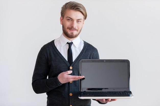 Twoja reklama tutaj! przystojny młody mężczyzna trzyma laptopa i wskazuje go, stojąc na szarym tle