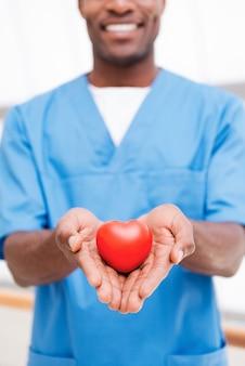Twoje serce we właściwych rękach. zbliżenie: pewny siebie młody afrykański lekarz w niebieskim mundurze, trzymający w dłoni rekwizyt serca i uśmiechnięty
