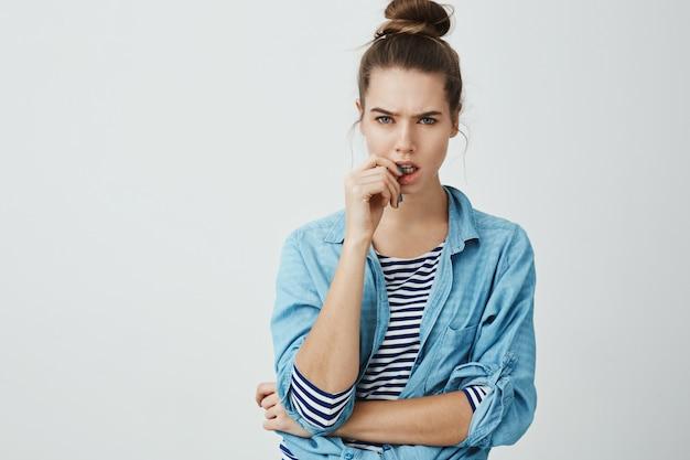 Twoje słowa nie pasują do prawdy. portret atrakcyjna młoda kobieta z kok fryzurą, marszcząc brwi i gryząc kciuk, patrząc z niedowierzaniem, stojąc