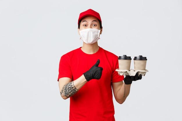 Twoje zamówienie jest gotowe, najlepsza kawa w mieście. azjatycki dostawca pokazuje kciuk w górę, dostarcza napoje do domu podczas pandemii covid 19, jest bezpieczny w domu i zamawia online, poleca serwis