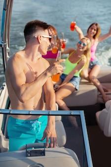 Twoje zdrowie. ciemnowłosy uśmiechnięty młody mężczyzna patrzący przez ramię na trzy wesołe dziewczyny siedzące za nim na pokładzie i pijące napoje bezalkoholowe