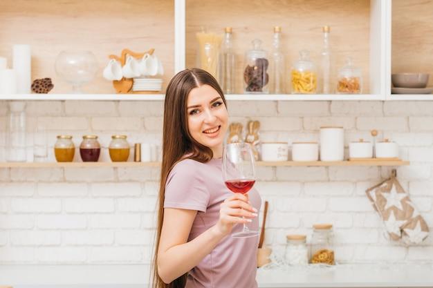 Twoje zdrowie. domowa zabawa. czas na odpoczynek. piękna młoda kobieta z kieliszkiem do wina. domowa przestrzeń kuchenna.