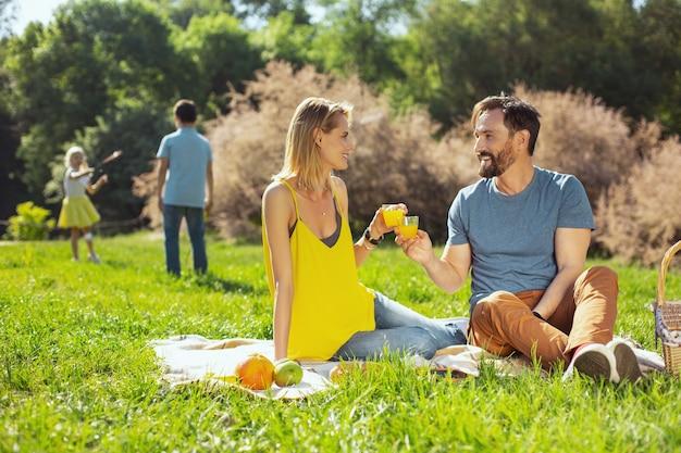 Twoje zdrowie. szczęśliwa kochająca żona uśmiechnięta i jej mąż i ich dzieci bawiące się w tle