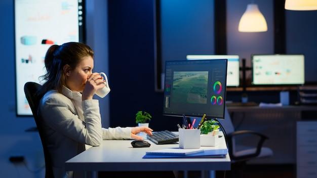 Twórca treści freelancer pracujący w godzinach nadliczbowych, aby dotrzymać terminu, siedząc przy biurku w biurze start-upu. kobieta kamerzysta edytowanie montażu filmu audio na profesjonalnym laptopie o północy.