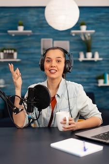 Twórca treści patrzący w kamerę podczas rozmowy do mikrofonu podczas podcastu kosmetycznego. kreatywny program online produkcja na żywo, gospodarz transmisji internetowej, transmitujący wideo na żywo, nagrywający cyfrową sieć społecznościową