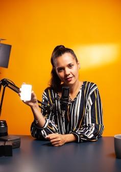 Twórca treści trzymający mini led i mówiący o tym podczas podcastu