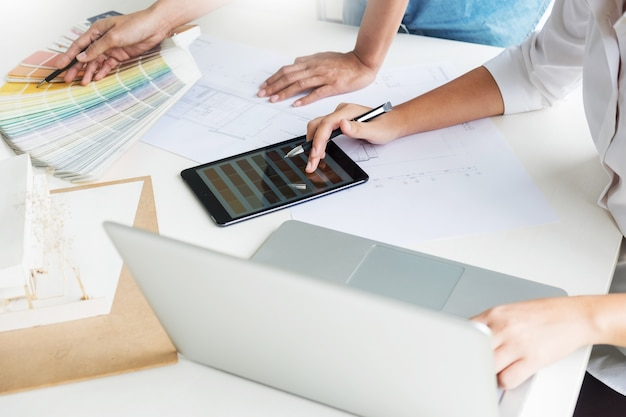 Twórcy kreatywni lub projektanci wnętrz z próbą pantone i planami budynku w biurze
