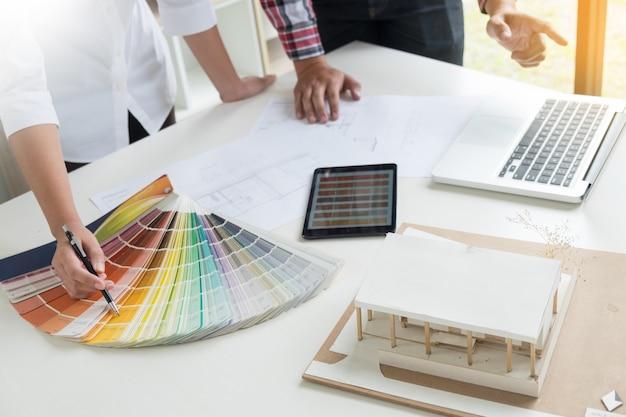 Twórcy kreatywni lub projektanci wnętrz z próbkami pantone i planami konstrukcyjnymi
