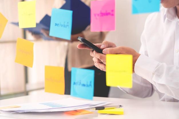 Twórcza grupa ludzi biznesu podczas burzy mózgów używa karteczek samoprzylepnych do dzielenia się pomysłami na szklanym oknie lub stole w biurze.