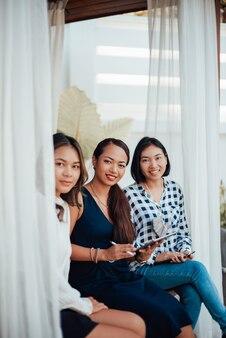 Twórcza praca projektantek. trzy azjatki w formalnym ubraniu pozują na wyciągnięcie ręki, patrząc na kamery i uśmiechając się.