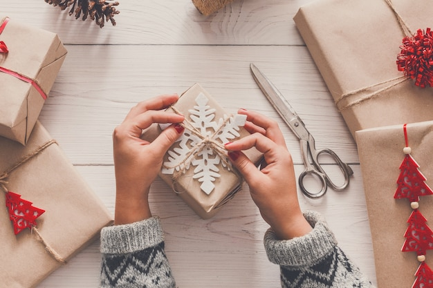 Twórcze hobby, kobiece dłonie zawijają świąteczny prezent ręcznie robiony w papier rzemieślniczy