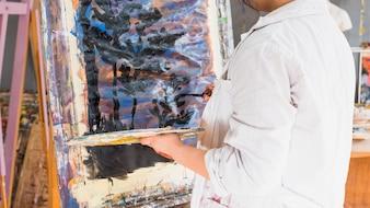 Twórczy artysta maluje na płótnie za pomocą czarnego pociągnięcia pędzlem
