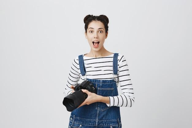 Twórczy podekscytowany fotograf dziewczyna trzymając aparat, robienie zdjęć
