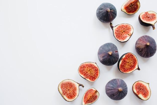 Twórczy wzór pokrojonych i całych dojrzałych fig na białym tle. ilustracja owoców. zdjęcie jedzenia. leżał płasko, widok z góry. skopiuj miejsce.