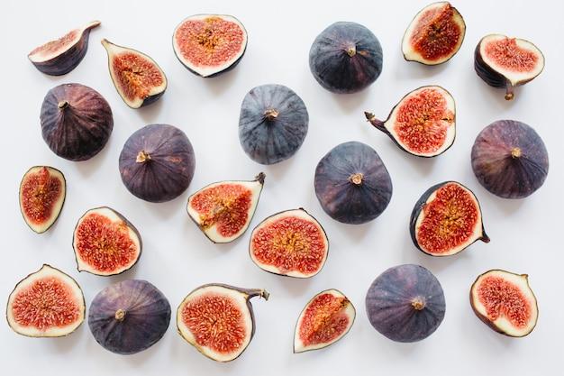 Twórczy wzór pokrojonych i całych dojrzałych fig na białym tle. ilustracja owoców. zdjęcie jedzenia. leżał płasko, widok z góry.