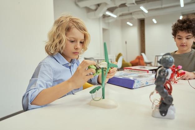 Twórz rzeczy kaukaski chłopiec badający zabawkę techniczną siedząc przy stole razem z innymi