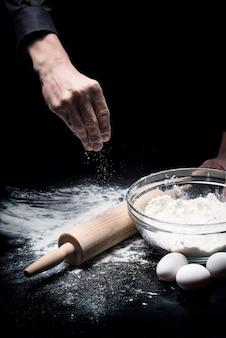 Tworzenie czegoś. zbliżenie dłoni mans przy użyciu mąki i jaj podczas pieczenia i gotowania w restauracji.