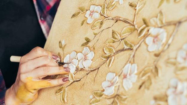 Tworzenie grafiki z motywem kwiatowym. talent i wyobraźnia artysty. kobieta malarz z narzędziem do modelowania. płótno na sztalugach.