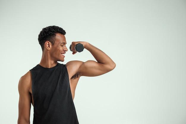 Tworzenie idealnego ciała. muskularny młody człowiek afryki ćwiczenia z hantlami i uśmiechnięty stojąc na szarym tle. strzał studio. koncepcja sportowa
