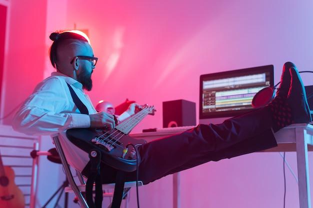 Tworzenie muzyki i koncepcji studia nagrań - brodaty gitarzysta nagrywa ścieżkę gitary elektrycznej