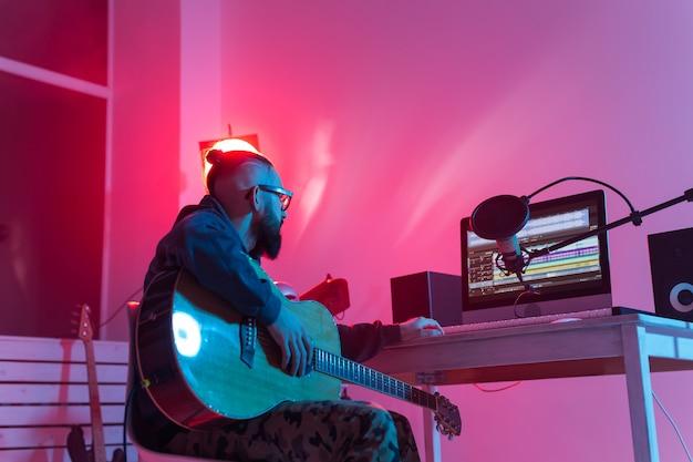 Tworzenie muzyki i koncepcji studia nagrań - brodaty gitarzysta zabawny człowiek nagrywający gitarę elektryczną