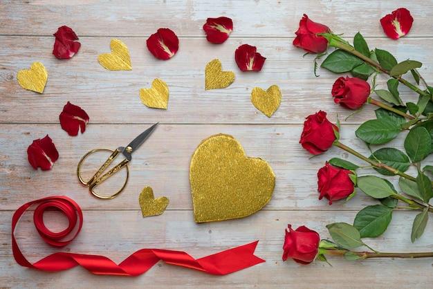 Tworzenie opakowań ze złotej folii pudełka w kształcie serca miłośnicy prezentów na drewnianych powierzchniach płatki róż