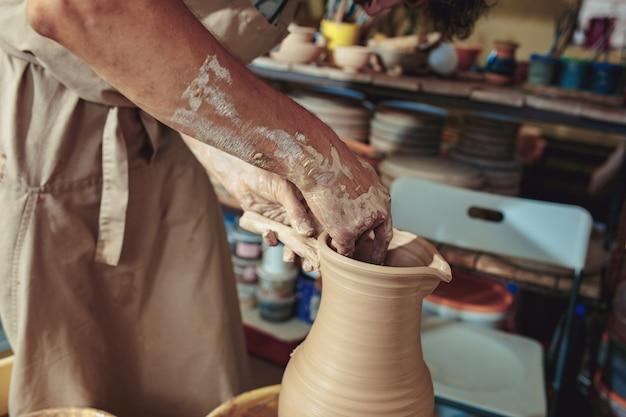Tworzenie słoika lub wazy z białej glinki z bliska. master crock. mężczyzna ręki robi glinianemu dzbankowi makro-.