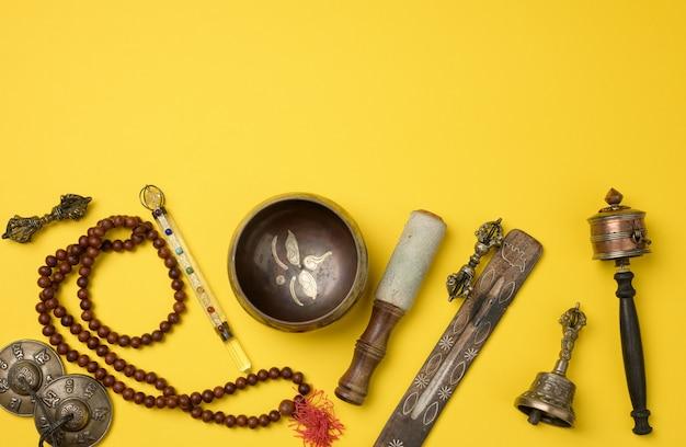 Tybetańska śpiewająca miedziana miska z drewnianą klapą na żółtym tle, obiekty do medytacji i medycyny alternatywnej, widok z góry, kopia przestrzeń