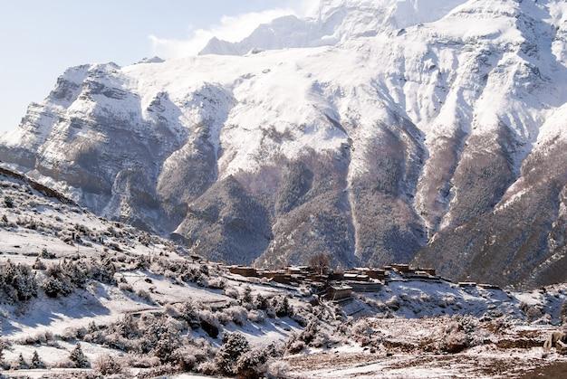 Tybetańska wioska pokryta śniegiem w himalajach z zaśnieżonym szczytem