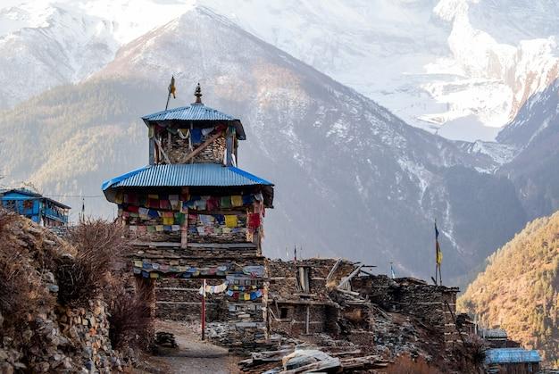 Tybetańska wioska w himalajach rano z śnieżnym szczytem