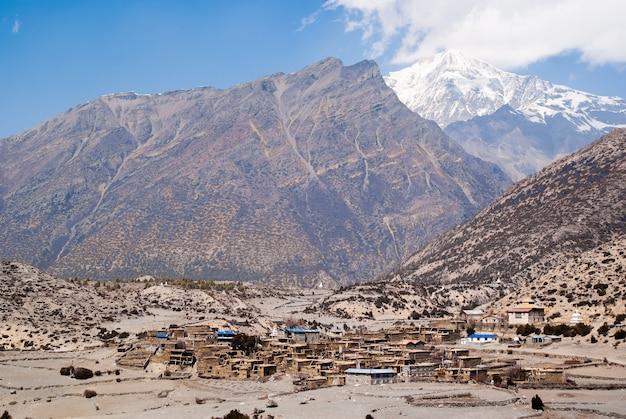 Tybetańska wioska w himalajach z śnieżnym szczytem