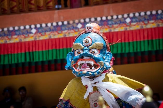 Tybetański mężczyzna ubrany w mistyczną maskę wykonuje taniec podczas buddyjskiego festiwalu w klasztorze hemis, ladakh, indie
