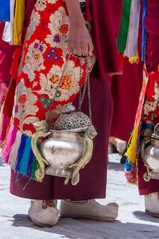 Tybetański mnich trzyma kadzielnicę, metalowe naczynie do palenia kadzideł, podczas kultu na buddyjskim festiwalu w klasztorze hemis, niedaleko leh, ladakh, północne indie, z bliska