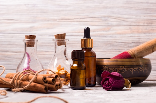 Tybetańskie miski do spania ustawione w butelkach: suche płatki róż, skórka pomarańczowa, oleje aromatyczne, sól morska, cynamon