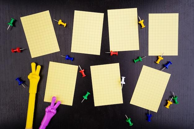 Tygodniowy harmonogram z szpilkami i dwoma długopisami na czarnym stole
