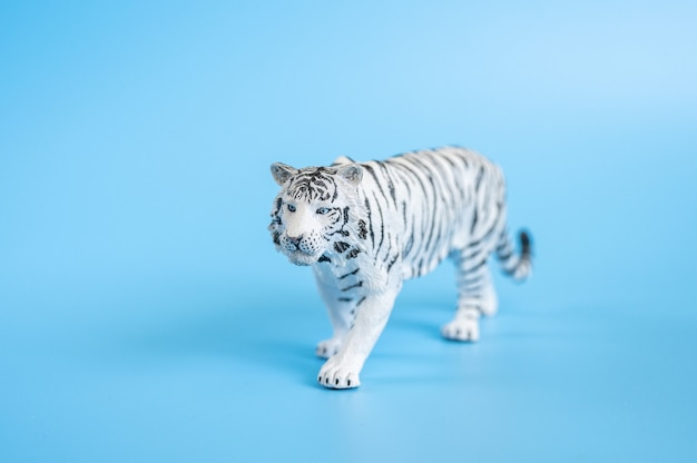Tygrys, symbol 2022 roku. plastikowa biała figurka tygrysa na niebieskim tle