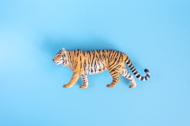 Tygrys, symbol 2022 roku. plastikowa zabawka pomarańczowy rysunek tygrysa na niebieskim tle. widok z góry