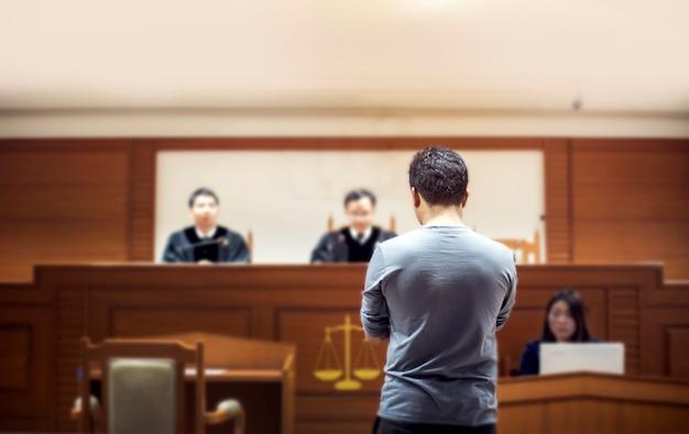 Tył attastora rozmawiającego z sędzią w sądzie