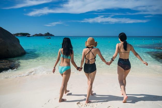 Tył azjatyckich młodych przyjaciół w strojach kąpielowych trzyma się za ręce i idzie razem do turkusowego morza andamańskiego. letnie wakacje na wyspie similan, phang nga, tajlandia. słynny cel podróży.