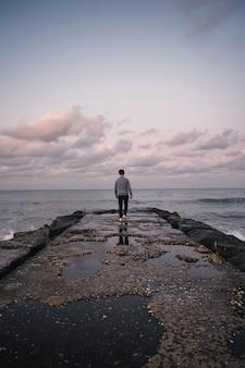 Tył azjatyckiego człowieka chodzącego na skalistym molo z uderzającą falą o zachodzie słońca na plaży jumunjin, gangwon-do, korea południowa