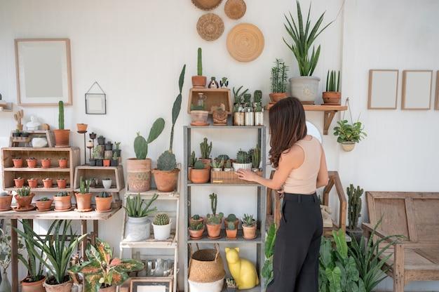 Tył azjatyckiej kobiety dotykającej kaktusa na drewnianej dekoracji prostoty półki w szklarni