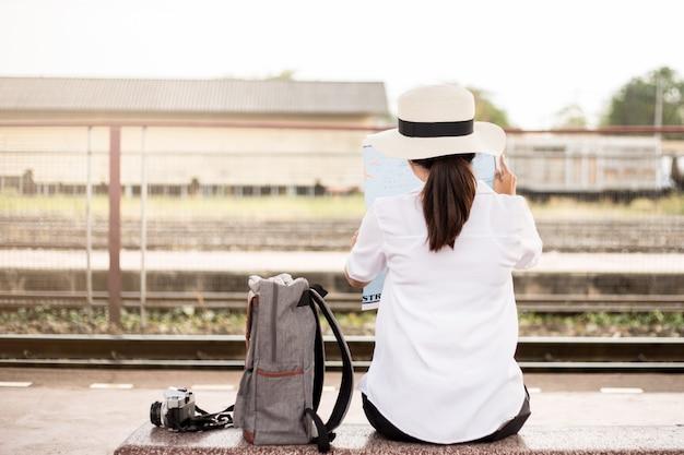 Tył azjatyckiej kobiety na stacji kolejowej na wakacjach.