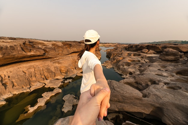 Tył azjatyckiej kobiety trzymającej się za ręce z parą na skalnym klifie w wielkim kanionie wieczorem. sam phan bok, ubon ratchathani